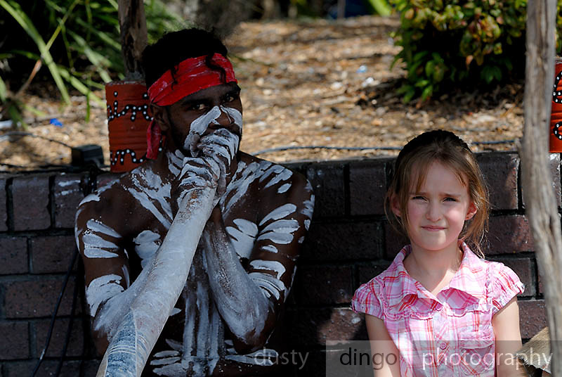 Young tourist (6 years old) sitting with male aboriginal busker playing didjeridoo. Circular Quay, Sydney, Australia