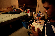 Higinio Lara reads his Bible before going to sleep as his roommates watch television. Lara, who is from Nayarit, Mexico, has worked at Titan Farms for ten years. Lara is married with two children, he said he misses his family so much that it brings him to tears at times.