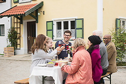 Family and friends enjoying outdoor party at farmhouse, Bavaria, Germany
