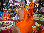 "06 APRIL 2015 - CHIANG MAI, CHIANG MAI, THAILAND: Monks help boys get into their monks' robes during their ordination on the last day of the three day long Poi Song Long Festival in Chiang Mai. The Poi Sang Long Festival (also called Poy Sang Long) is an ordination ceremony for Tai (also and commonly called Shan, though they prefer Tai) boys in the Shan State of Myanmar (Burma) and in Shan communities in western Thailand. Most Tai boys go into the monastery as novice monks at some point between the ages of seven and fourteen. This year seven boys were ordained at the Poi Sang Long ceremony at Wat Pa Pao in Chiang Mai. Poy Song Long is Tai (Shan) for ""Festival of the Jewel (or Crystal) Sons.   PHOTO BY JACK KURTZ"