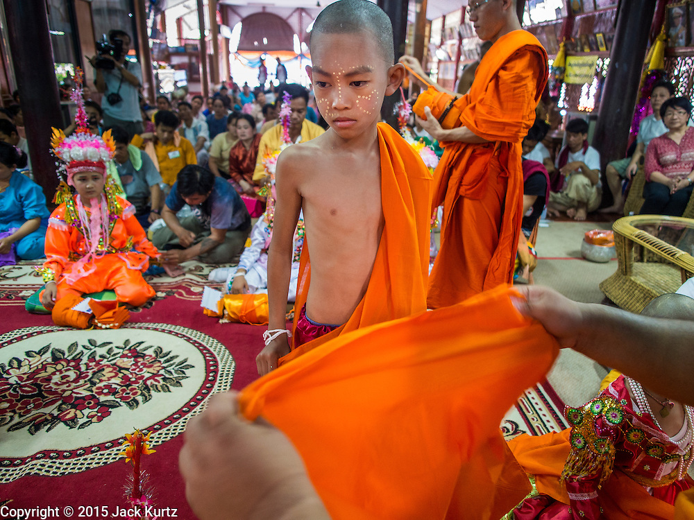 """06 APRIL 2015 - CHIANG MAI, CHIANG MAI, THAILAND: Monks help boys get into their monks' robes during their ordination on the last day of the three day long Poi Song Long Festival in Chiang Mai. The Poi Sang Long Festival (also called Poy Sang Long) is an ordination ceremony for Tai (also and commonly called Shan, though they prefer Tai) boys in the Shan State of Myanmar (Burma) and in Shan communities in western Thailand. Most Tai boys go into the monastery as novice monks at some point between the ages of seven and fourteen. This year seven boys were ordained at the Poi Sang Long ceremony at Wat Pa Pao in Chiang Mai. Poy Song Long is Tai (Shan) for """"Festival of the Jewel (or Crystal) Sons.   PHOTO BY JACK KURTZ"""