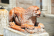 Lion statue from the destoyed south door of the 12th century Romanesque Ferrara Duom, Italy . Ferrara Cathedral (Basilica Cattedrale di San Giorgio, Duomo di Ferrara) is a Roman Catholic cathedral and minor basilica in Ferrara, Northern Italy. The original Romanesque design of Ferrara Cathedral is manifest in the façade. In the centre of the façade of Ferrara Cathedral is a porch, supported by two columns with Atlases seated on lions at the bases. It is decorated with a Last Judgement by an unknown master and a loggia with a Madonna and Child (a late Gothic addition). The portal of Ferrara Cathedral is the work of the sculptor Nicholaus, a pupil of Wiligelmus. The lunette shows Saint George, patron saint of Ferrara, slaying the dragon; scenes from the Life of Christ appear on the lintel. The jambs framing the entrance of Ferrara Cathedral are embellished with figures depicting the Annunciation and the four prophets who foretold the coming of Christ.<br /> <br /> Visit our ITALY PHOTO COLLECTION for more   photos of Italy to download or buy as prints https://funkystock.photoshelter.com/gallery-collection/2b-Pictures-Images-of-Italy-Photos-of-Italian-Historic-Landmark-Sites/C0000qxA2zGFjd_k<br /> <br /> If you prefer to buy from our ALAMY PHOTO LIBRARY  Collection visit : https://www.alamy.com/portfolio/paul-williams-funkystock/ferrara.html .