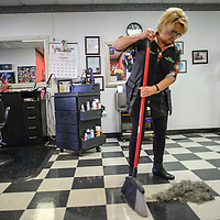 Clorinda Brito sweeps up hair from Grants mayor Modie Hicks at Clo's Hair Design in Grants Thursday. Hicks had his hair cut after a fundraiser to benefit the Marine ROTC drill team trip to a national competition.