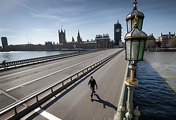 FILE IMAGE © Licensed to London News Pictures. 24/03/2020. London, UK. A few pedestrians can be seen on an almost deserted Westminster Bridge at 1:14pm  after Prime Minister Boris Johnson announced that the UK will now lockdown in order to fight the spread of the coronavirus. Only essential journeys for food and one period of excercise will be allowed per day. Photo credit: Peter Macdiarmid/LNP