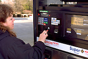 Woman age 54 using automated credit card gas pump.  WesternSprings  Illinois USA