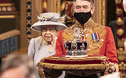 Queen Elizabeth II proceeds through the Royal Gallery before delivering the her speech during the State Opening of Parliament in the House of Lords at the Palace of Westminster in London. Picture date: Tuesday May 11, 2021.