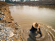 """01 APRIL 2016 - WANG NUEA, LAMPANG, THAILAND:  A man pans for gold in the Mae Wang. Villagers in the Wang Nuea district of Lampang province found gold in the Mae Wang (Wang River) in 2011 after excavation crews dug out sand for a construction project. A subsequent Thai government survey of the river showed """"a fair amount of gold ore,"""" but not enough gold to justify commercial mining. Now every year when the river level drops farmers from the district come to the river to pan for gold. Some have been able to add to their family income by 2,000 to 3,000 Baht (about $65 to $100 US) every month. The gold miners work the river bed starting in mid-February and finish up by mid-May depending on the weather. They stop panning when the river level rises from the rains. This year the Thai government is predicting a serious drought which may allow miners to work longer into the summer. The 2016 drought has lowered the water level so much that the river is dry in most places and people can only pan for gold in a very short stretch of the river.     PHOTO BY JACK KURTZ"""