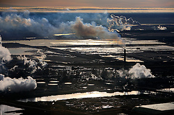 CANADA ALBERTA FORT MCMURRAY 28SEP09 - Aerial view of Syncrude upgrader in the Boreal forest north of Fort McMurray, northern Alberta, Canada.....The tar sand deposits lie under 141,000 square kilometres of sparsely populated boreal forest and muskeg and contain about 1.7 trillion barrels of bitumen in-place, comparable in magnitude to the world's total proven reserves of conventional petroleum. ..Current projections state that production will  grow from 1.2 million barrels per day (190,000 m³/d) in 2008 to 3.3 million barrels per day (520,000 m³/d) in 2020 which would place Canada among the four or five largest oil-producing countries in the world...The industry has brought wealth and an economic boom to the region but also created an environmental disaster downstream from the Athabasca river, polluting the lakes where water and fish are contaminated. The native Indian tribes of the Mikisew, Cree, Dene and other smaller First Nations are seeing their natural habitat destroyed and are largely powerless to stop or slow down the rapid expansion of the oil sands development, Canada's number one economic driver.....jre/Photo by Jiri Rezac / GREENPEACE....© Jiri Rezac 2009