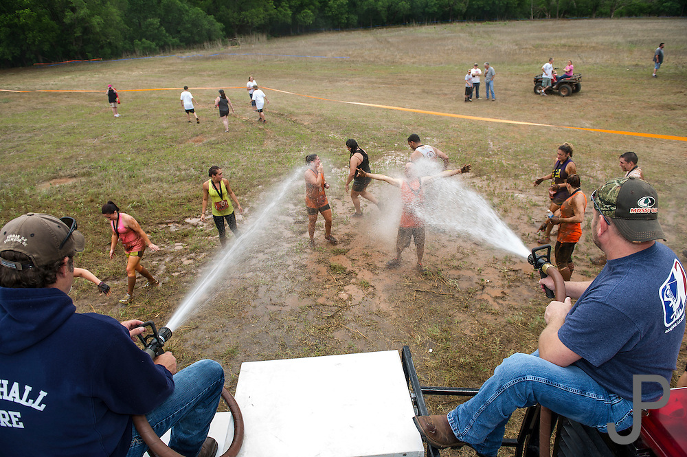Fireman from Mulhall Volunteer Fire Department hose down participants after they complete their run.