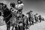 In black and white, a group of Kazakh eagle hunters riding through the village together with their eagles wearing their bright red fur hats,  Altai Mountains, Bayan Ulgii, Mongolia