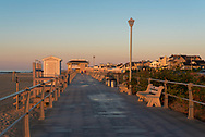 Joggers are on the boardwalk early in the morning under a soft summer light