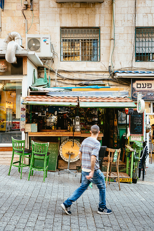 A Jewish man passes in front of Jimmy's Parliament, a bar in the Mahane Yehuda Market in Jerusalem, Israel, on November 21, 2019.