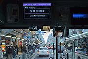 Shijo Kawaramachi, a vibrant part of central Kyoto, Japan where Shijō and Kawaramachi Streets intersec, seen through a bus window.