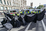 Seven 'Oil Slicks' activists dressed in black-clads enact a performance in front of the Police outside Houses of Parliament nearby Parliament Gardens, Westminster as they march against 'ecocide' seeking to step up pressure on Shell and demand an end on fossil fuel extraction on Tuesday, Sept 8, 2020 - Extinction Rebellion activists staged a performative protest enacting a crime scene outside Shell Headquarters in Jubilee Gardens, central London. Environmental nonviolent activists group Extinction Rebellion enters its 8th day of continuous ten days protests to disrupt political institutions throughout peaceful actions swarming central London into a standoff, demanding that central government obeys and delivers Climate Emergency bill. (VXP Photo/ Vudi Xhymshiti)