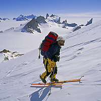 Filchner Mountains, Queen Maud Land, Antarctica. An expedition skier ascends Mount Kubus in front of Troll's Castle.