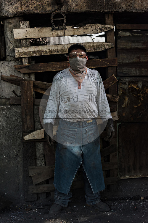 Portrait of an indigenous Purepecha coppersmith a copper workshop in Santa Clara del Cobre, Michoacan, Mexico. The Purepecha people have been crafting copper crafts since the 12th century.