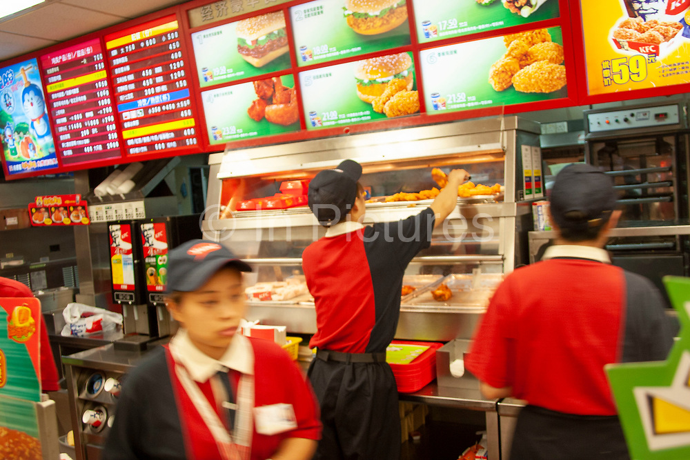 KFC (Kentucky Fried Chicken) burger at a restaurant on Huai Hai Road and Shaanxi Road in Shanghai's downtown shopping district. Western fast food is popular amongst the young as are many western influences on this society that has changed dramatically since the late 1990's, embracing western culture, fashion, food and attitudes. These restaurants are always full, despite being more expensive than fast Chinese food. There are many overweight youngsters in Shanghai, something of a recent characteristic as dietary changes result in a generally larger generation.