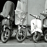 Several scooters parked on the street in Florence, Italy