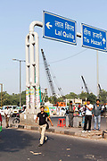 A man crosses the road amidst traffic and construction work by the ISBT bus station, Delhi, India