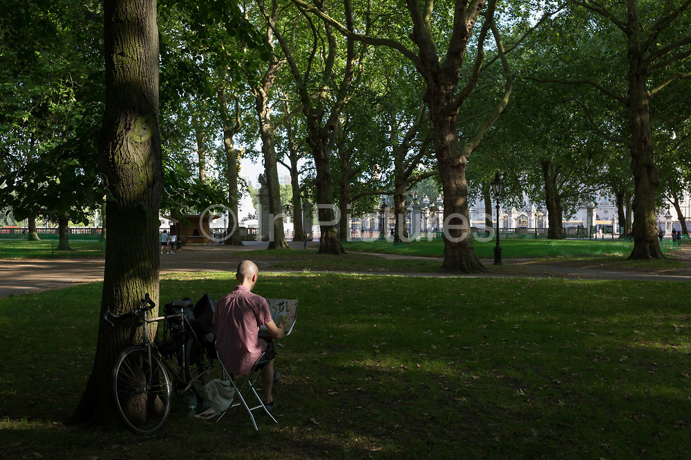With a further 184 reported UK Covid deaths in the last 24 hrs, a total now of 43,414, an artist creates art with Buckingham Palace in Green Park within view during the last stages of the pandemic, on 26th June 2020, in London, England. Many have found lockdown as an opportunity to be more creatively active and closer to the natural world. Government restrictions on the 2 metre rule is to be realxed on 4th July and replaced with one metre plus in the hope it stimulates the struggling UK economy.
