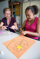 Teacher helping student with learning disability in art class,