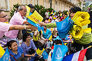 01 AUGUST 2013 - BANGKOK, THAILAND: Thais buy the yellow flag of the Thai monarchy in front of Siriraj Hospital, before Bhumibol Adulyadej, the King of Thailand, left the hospital Thursday. The King, 85, was discharged from Bangkok's Siriraj Hospital, where he has lived since September 2009. He traveled to his residence in the seaside town of Hua Hin, about two hours drive south of Bangkok, with his wife, 80-year-old Queen Sirikit, who has also been treated in the hospital for a year.      PHOTO BY JACK KURTZ