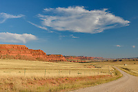Bar-C Road in Barnum, Wyoming passes between massive ranches flanked by red cliffs.