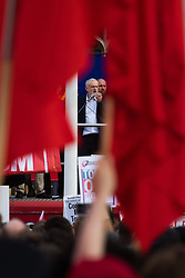 Parliament Square, Westminster, London, June 27th 2016. Thousands of Labour's Momentum members and their supporters gather in Parliament Square in a display of support for embattled Labour Leader Jeremy Corbyn as he suffers numerous calls for his resignation by party members, saying he has does not have the authority to lead the divided party, following his less than emphatic support for Remain in the EU referendum. PICTURED: Seen between waving red flags, Corbyn addresses the crowd.