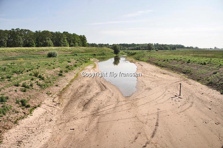 Nederland, Slijk-Ewijk, 26-5-2020 De opening, inlaat in de zomerdijk van de loenensche buitenpolder in de betuwe staat droog omdat het water in de waal langzaam zakt vanwege de aanhoudende droogte in haar stroomgebied.  Het natuurgebied in de uiterwaarden is aangelegd in het kader van ruimte voor de rivier, maar staat nu bijna droog . Langzaam daalt het peil van het water in de rivier In de herfst van 2018 stond de stand bij Lobith op 6,55 meter boven nap, een laagwater record dat veel overlast voor de binnenvaart opleverde .. . Die stand is nu nog 7,80 meter . In de maas wordt vanaf zuid Limburg het waterpeil kunstmatig geregeld via de stuwen en sluizen en is pas bij minimale aanvoer vanuit belgie grote verlaging zichtbaar. Foto: Flip Franssen
