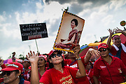 10 MAY 2014 - BANGKOK, THAILAND: A supporter of Yingluck Shinawatra holds up a photo of the ousted Prime Minister at a rally in Bangkok. Thousands of Thai Red Shirts, members of the United Front for Democracy Against Dictatorship (UDD), members of the ruling Pheu Thai party and supporters of the government of ousted Prime Minister Yingluck Shinawatra are rallying on Aksa Road in the Bangkok suburbs. The government was ousted by a court ruling earlier in the week that deposed Yingluck because the judges said she acted unconstitutionally in a personnel matter early in her administration. Thailand now has no functioning government. Red Shirt leaders said at the rally Saturday that any attempt to impose an unelected government on Thailand could spark a civil war. This is the third consecutive popularly elected UDD supported government ousted by the courts in less than 10 years.    PHOTO BY JACK KURTZ