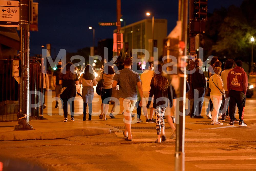 Pedestrians walk in downtown Chicago under orange street lights in Chicago, Illinois. Photo by Mark Black