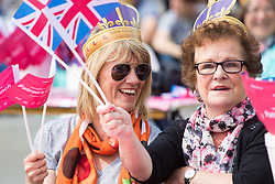 Trafalgar Square, London, June 12th 2016. Rain greets Londoners and visitors to the capital's Trafalgar Square as the Mayor hosts a Patron's Lunch in celebration of The Queen's 90th birthday. PICTURED: Two women get into the patriotic spirit of the occasion.