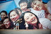 A mother and child pose for a photo next to an advertisement showing smiling Chinese youth. Advertising space in Beijing has been replaces with signs and posters heralding the coming of the August 8th, summer Olympics, featuring smiling people as well as traditional Chinese themes, such as Peking Opera.