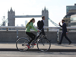 Commuters cross London Bridge, which has reopened after Saturday evening's terror attack.