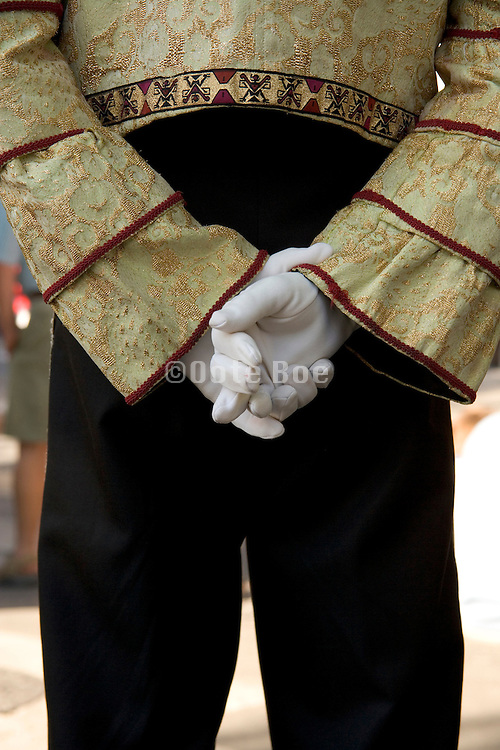 man standing hands clasped behind his back wearing white gloves