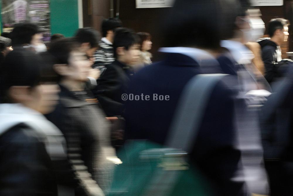 Japanese school children in uniform walking in a crowded street