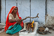 Rajasthani village woman preparing cooking fire in the morning. Pushkar, Rajasthan. INDIA