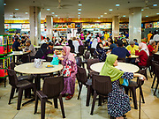 "13 DECEMBER 2018 - SINGAPORE:The ""hawker stalls"" in the Joo Chiat complex in the Geylang neighborhood. Joo Chiat is a multi-tower high rise residential estate. Hawker stalls used to be street food stalls, but the government of Singapore has moved them into permanent food courts. There are hawker food stalls and retail businesses on the ground floor and residences on the upper levels.  The Geylang area of Singapore, between the Central Business District and Changi Airport, was originally coconut plantations and Malay villages. During Singapore's boom the coconut plantations and other farms were pushed out and now the area is a working class community of Malay, Indian and Chinese people. In the 2000s, developers started gentrifying Geylang and new housing estate developments were built.   PHOTO BY JACK KURTZ"