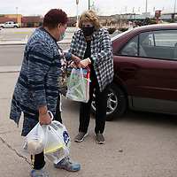 Mona Fraiser, left, receives food donations from Sally Carter at St. Paul Missionary Baptist Church during their food drive benefiting the Community Pantry Monday in Gallup. Fraiser organized the food drive in honor of Dr. Martin Luther King Jr. day in place of their annual celebration due to COVID-19 restrictions.