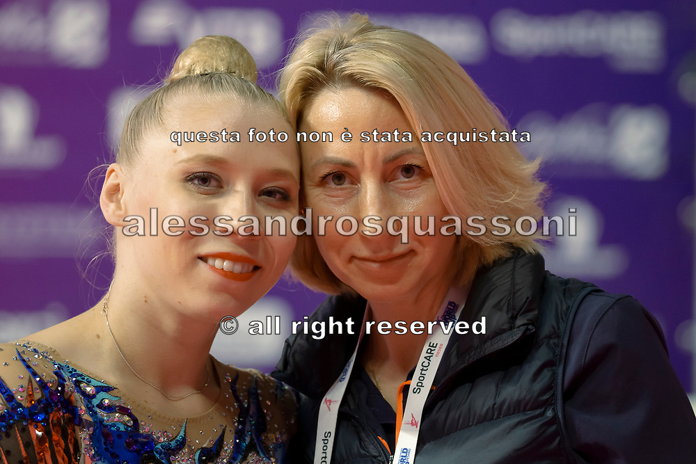 Kseniya Moustafaeva sitting at Kiss and Cry, together with her coach and mother, of the Rhythmic Gymnastics World Cup in Pesaro.