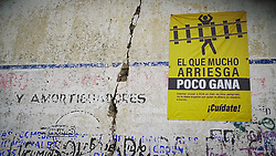 A poster in Huamantla, Mexico says: 'el que mucho arriesga poco gana... cuídate' - he who risks a lot gains little, take care. The image shows someone cut in half on the rail tracks. Many migrants are killed and injured in accidents on the rail network known as La Bestia in Mexico.