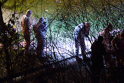 © Licensed to London News Pictures. 28/12/2011. Salford, UK. The flash from a forensic investigater's camera fires as they continue to work in to the night looking for evidence following the murder of Indian student Anuj Bidve. They search through a small patch of wasteland on the corner of Ordsall Lane and Asgard Drive, in bushes and through trees, by torchlight. The 23 year old Lancaster University student was shot on Boxing Day. Photo credit : Joel Goodman/LNP