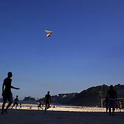 Locals play beach football during the late afternoon sunshine at Sao Conrado beach as a hang glider prepares to land on the beach, Rio de Janeiro,  Brazil. 8th July 2010. Photo Tim Clayton...
