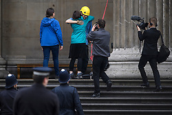 © Licensed to London News Pictures. 19/05/2016. London, UK. A climber who scaled the building being embraced by friends after climbing down. A Greenpeace protest by Greenpeace at the British museum which has closed the museum. Greenpeace climbers have scaled pillars at the museum, erecting banners protesting against BP sponsorship of Sunken Cities: Egypts - Lost Worlds exhibition at the museum. ‎Photo credit: Ben Cawthra/LNP