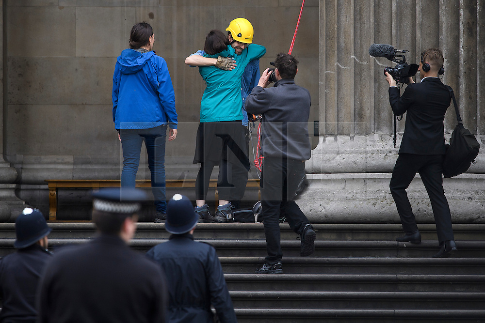 © Licensed to London News Pictures. 19/05/2016. London, UK. A climber who scaled the building being embraced by friends after climbing down. A Greenpeace protest by Greenpeace at the British museum which has closed the museum. Greenpeace climbers have scaled pillars at the museum, erecting banners protesting against BP sponsorship of Sunken Cities: Egypts - Lost Worlds exhibition at the museum. Photo credit: Ben Cawthra/LNP