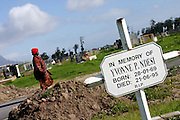 A woman is walking across the Guguletu cemetery, just off Guguletu township in Cape Town. Many of the people who died of AIDS in the nearby area are buried here. South Africa is also claiming to have no land left for the dead and many people are in fact buried on top of others.
