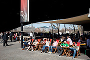 Scene along the Southbank on a spring afternoon, London. People relaxing in deck chairs outside the BFI cinema under Waterloo Bridge. South Bank is an area of London, England located immediately adjacent to the south bank of the River Thames. It forms a long and narrow section of riverside development that is within the London Borough of Lambeth and partly in the London Borough of Southwark. It developed much more slowly than the north bank of the river due to adverse conditions, and throughout its history has twice functioned as an entertainment district, separated by a hundred years of use as a location for industry. The South Bank is a significant arts and entertainment district.