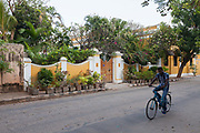 A man cycles past a Colonial house with many plants and flowers outside, Pondicherry, India. Pondicherry now Puducherry is a Union Territory of India and was a French territory until 1954 legally on 16 August 1962. The French Quarter of the town retains a strong French influence in terms of architecture and culture.