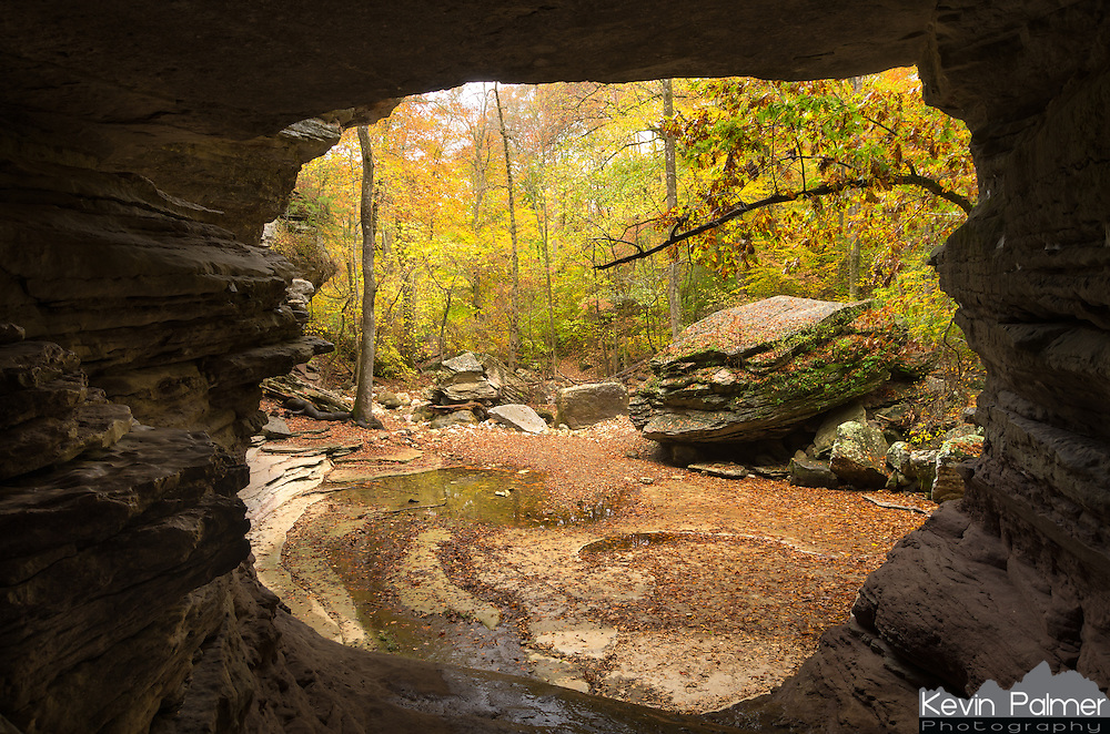 Lost Valley in Arkansas is full of wonders such as towering cliffs, massive boulders, caves, and, waterfalls. This picture was taken inside a natural bridge, looking out at the colorful forest. During the dry season Clark Creek flows underground. The water comes to the surface at the other side of this natural bridge. It flows through and then ends in this pool where it seeps back under the earth. Even though it was raining quite a bit on this evening it didn't make the creek rise any higher.