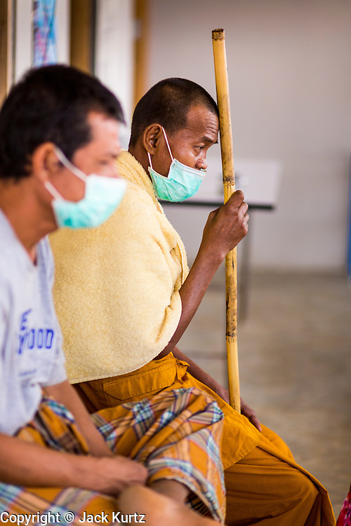 03 MARCH 2104 - MAE KASA, TAK, THAILAND: Patients, including a Buddhist monk at right, wait for their tuberculosis medication at the Sanatorium Center for Border Communities in Mae Kasa, about 30 minutes north of Mae Sot, Thailand. The Sanatorium provides treatment and housing for people with tuberculosis in an isolated setting for about 68 patients, all Burmese. The clinic is operated by the Shoklo Malaria Research Unit and works with several other NGOs that assist Burmese people in Thailand. Reforms in Myanmar have alllowed NGOs to operate in Myanmar, as a result many NGOs are shifting resources to operations in Myanmar, leaving Burmese migrants and refugees in Thailand vulnerable. Funding cuts could jeopardize programs at the clinic. TB is a serious health challenge in Burma, which has one of the highest rates of TB in the world. The TB rate in Thailand is ¼ to ⅕ the rate in Burma.        PHOTO BY JACK KURTZ